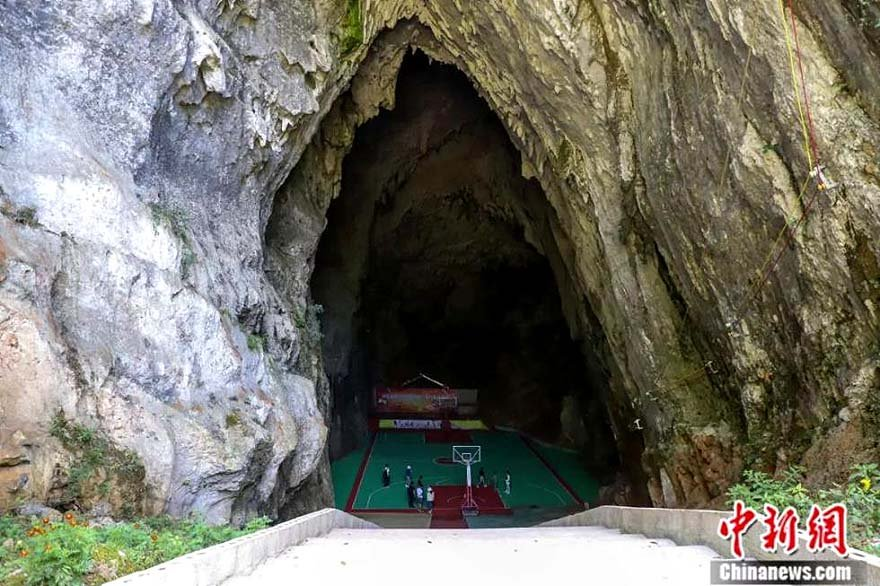 A basketball field inside a cave in mountainous Guizhou province. People from a mountain village have transformed a Karst cave into a basketball court, equipped with an electronic lighting system and a tiered seating area that can accommodate over a thousand audience.