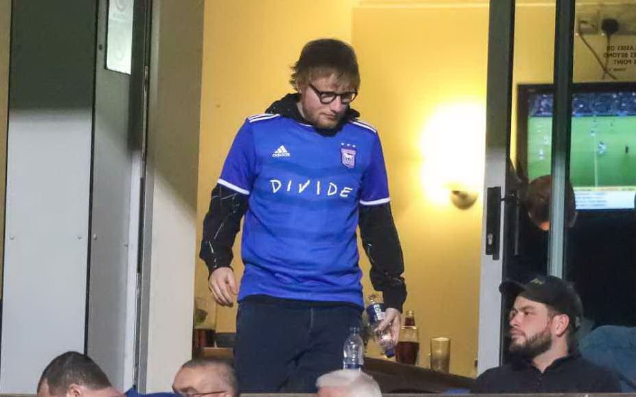 Ed Sheeran at the #itfc game tonight wearing his new personalised Town shirt #EdSheeran     From memory Town's record when he's been here isn't very good...  Pic from @Stephen_Waller<br>http://pic.twitter.com/NE0cY0nasw