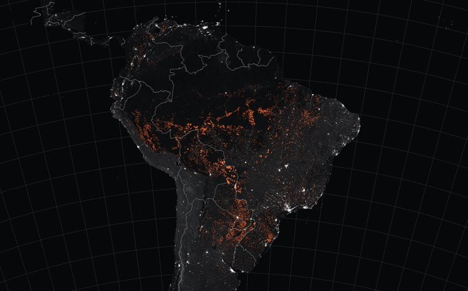 Black and white satellite image of South America with orange dots showing active burning fire pixels