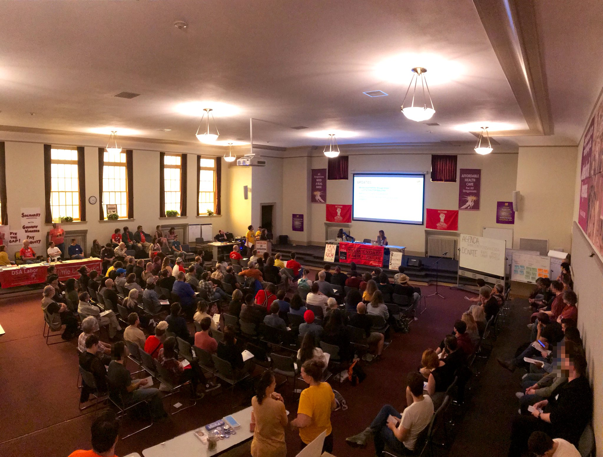 Photo of the September general meeting. 130 socialists in the room. DSA Banners strewn about.