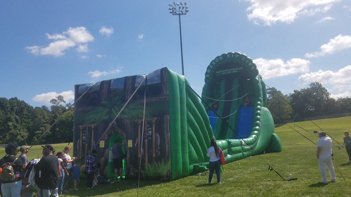 Lots of people enjoying Zip Line rides and Trackless Train by Backyard Inflatables ($5)!