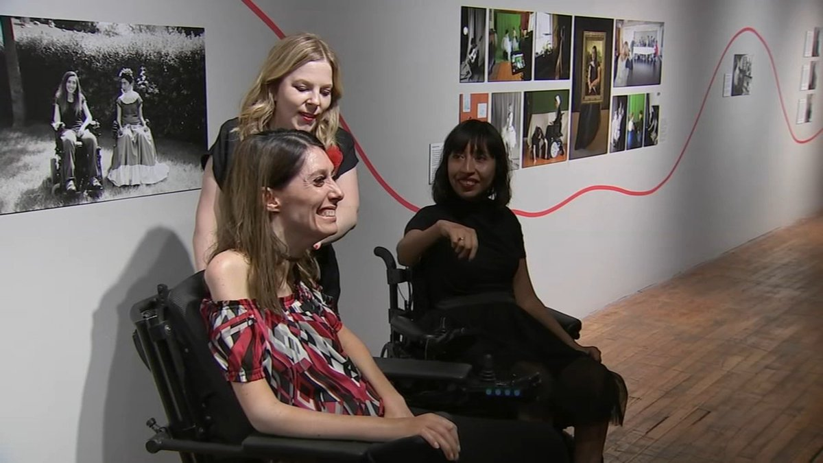 Three women smile as they pose in front of a gallery wall with photographs. Two women with brown hair, both wheelchair users, pose on either side of a woman with blonde hair.