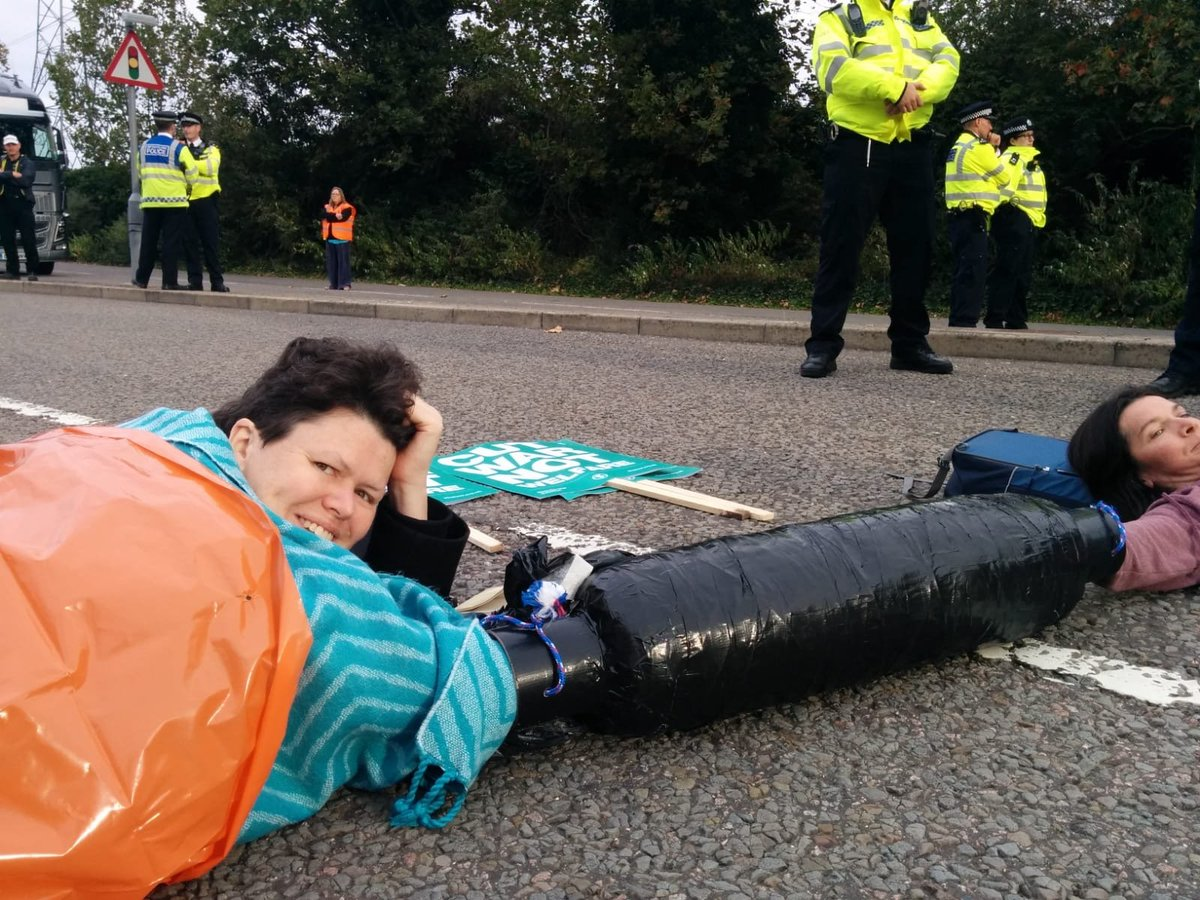 """@CClimateAction's Angela locked on this morning to stop the set up of the DSEI arms fair at London's ExCel. As the climate and ecological emergency worsens more & more people will be queuing up to profit from social collapse and warfare.""  #HumansOfXR #ExtinctionRebellion<br>http://pic.twitter.com/AwcJsjJsyA"