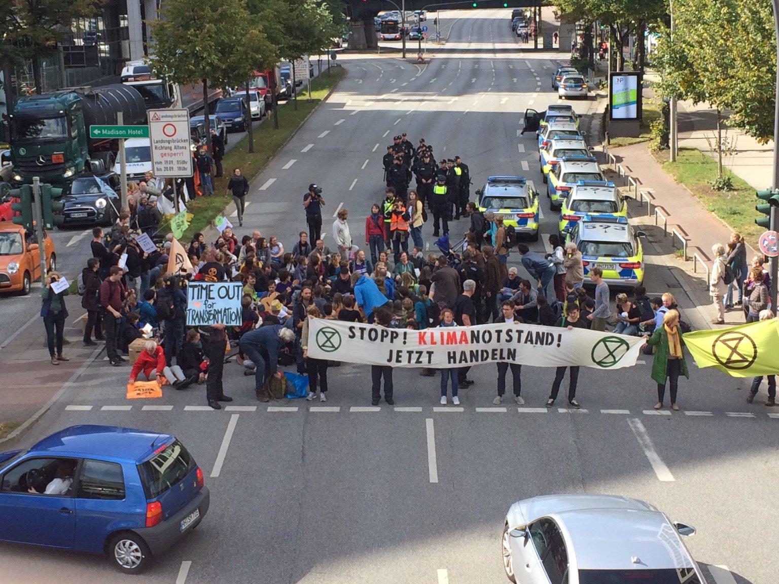 Demonstrierende Personen, die mit Bannern die Straße sperren