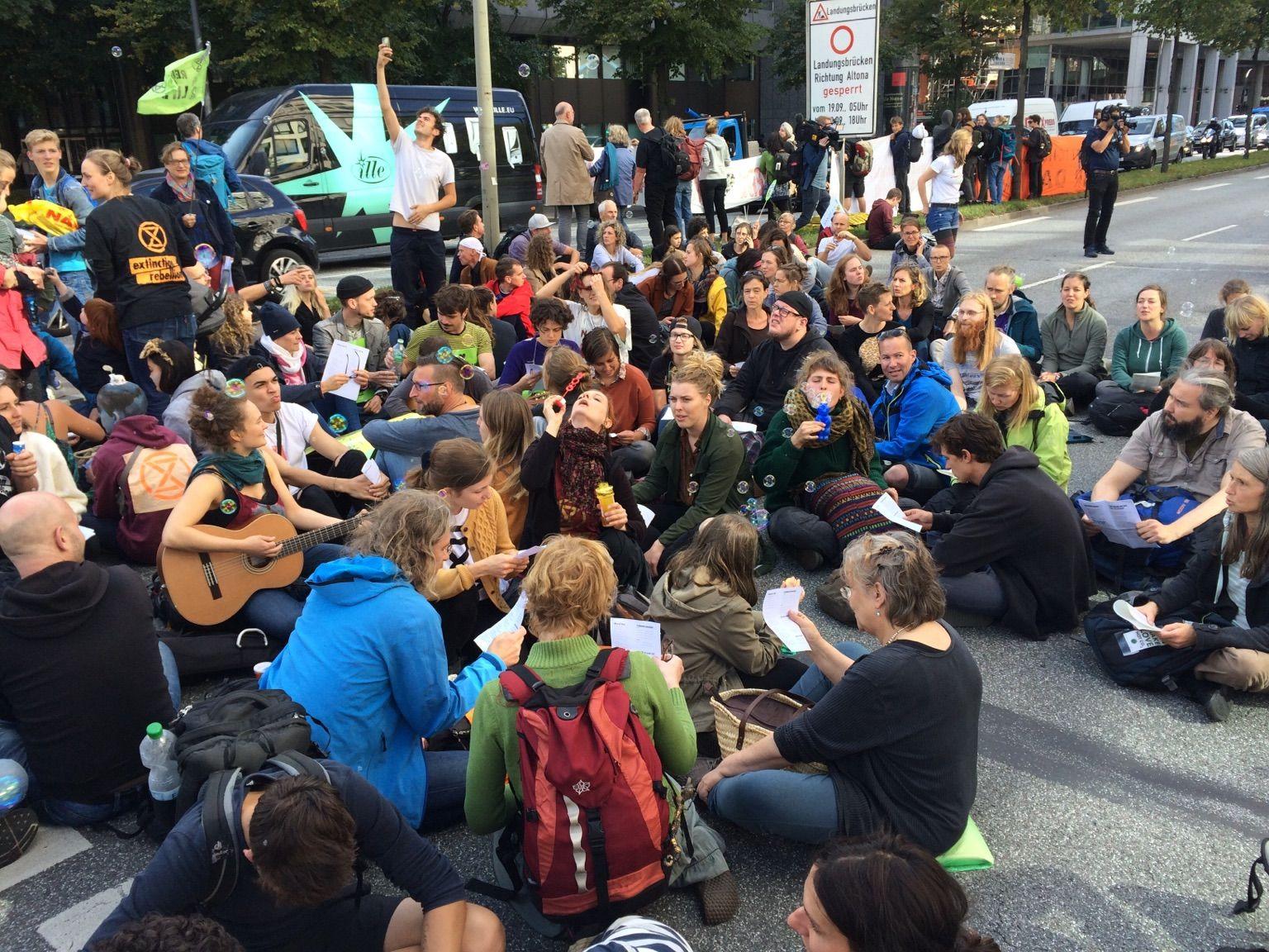 Auf der Straße sitzende Personen, die gemeinsam singen