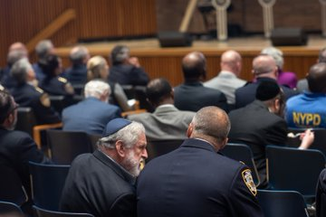 A Jewish man and a police officer sit together, talking.