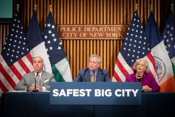 Mayor de Blasio sits at a table with a sign saying Safest Big City with a detective and the director of the Office for the Prevention of Hate Crimes.