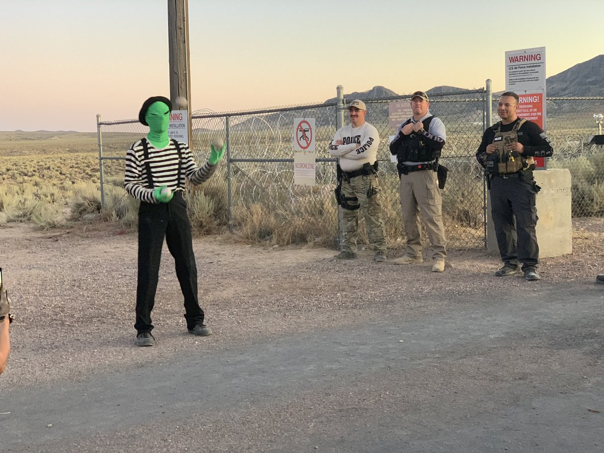 An alien entertaining law enforcement at the back security gate of Area 51. #area51 #StormingArea51 <br>http://pic.twitter.com/JADpsch4F6