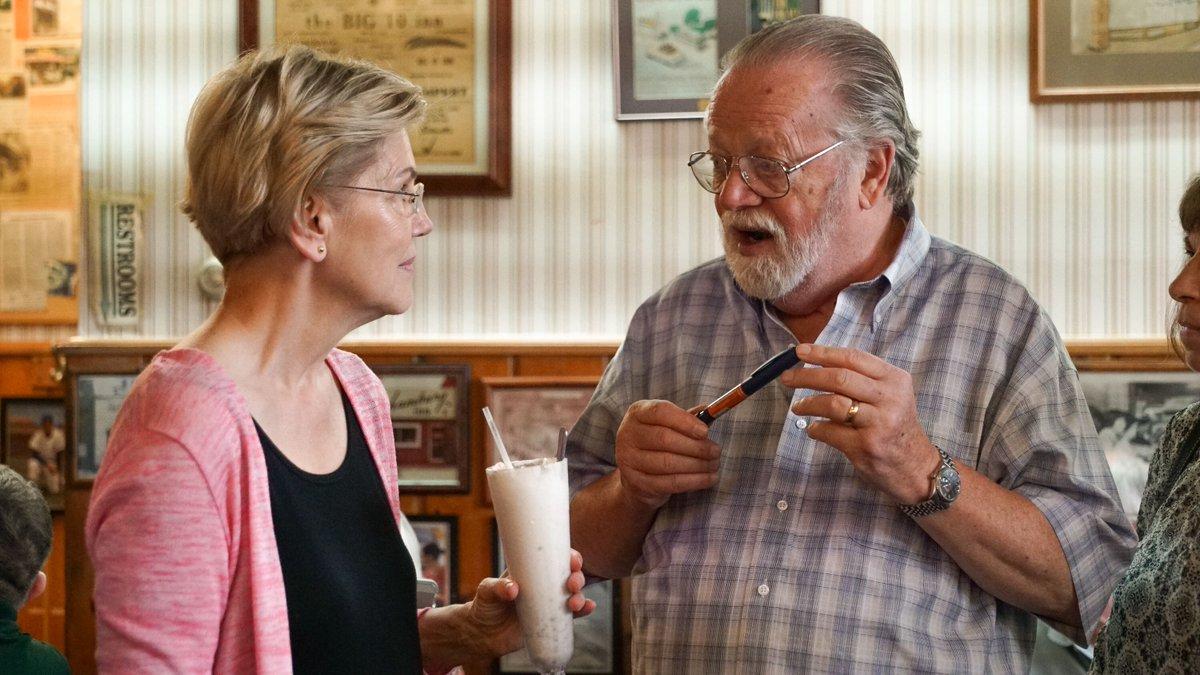 Elizabeth Warren holds a milkshake while talking to Iowa voters.