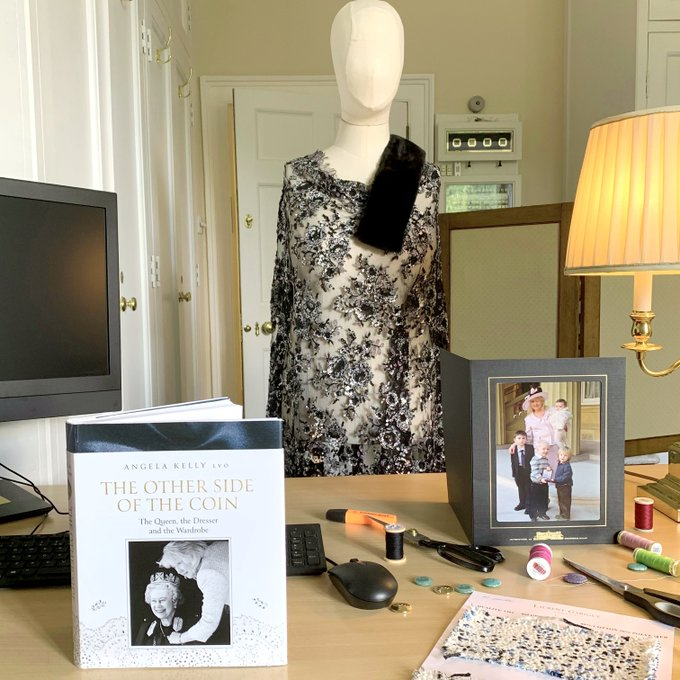 A photo of 'The Other Side of the Coin' stood up on a desk next to a mannequin, with buttons and thread scattered about.
