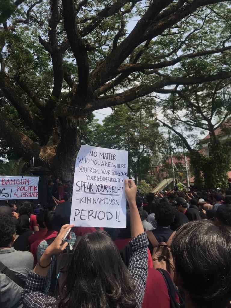 Seorang pengunjuk rasa di Malang membawa kertas bertuliskan kutipan RM BTS dalam aksi demo, Selasa (24/9/2019).