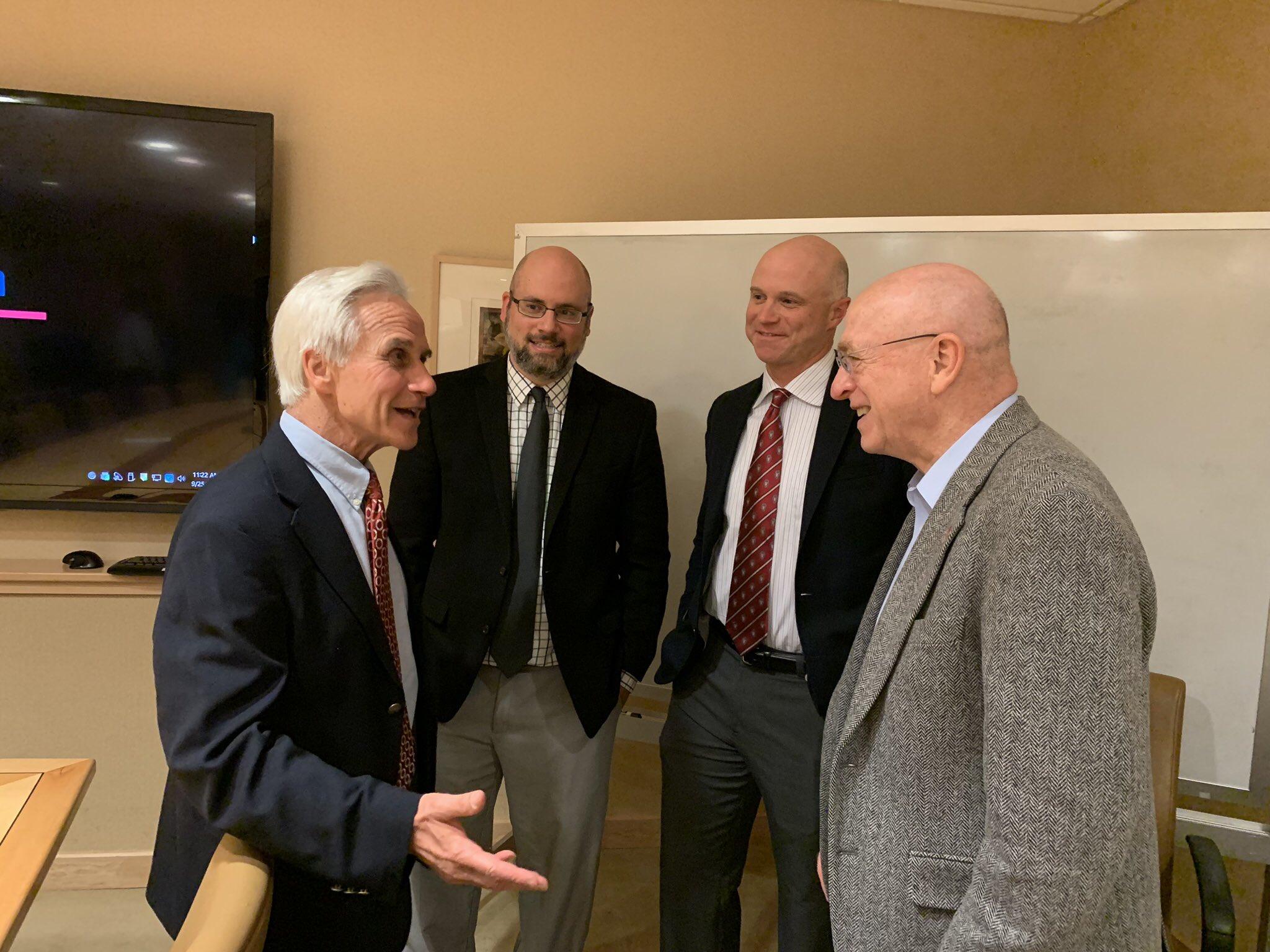 four men speaking