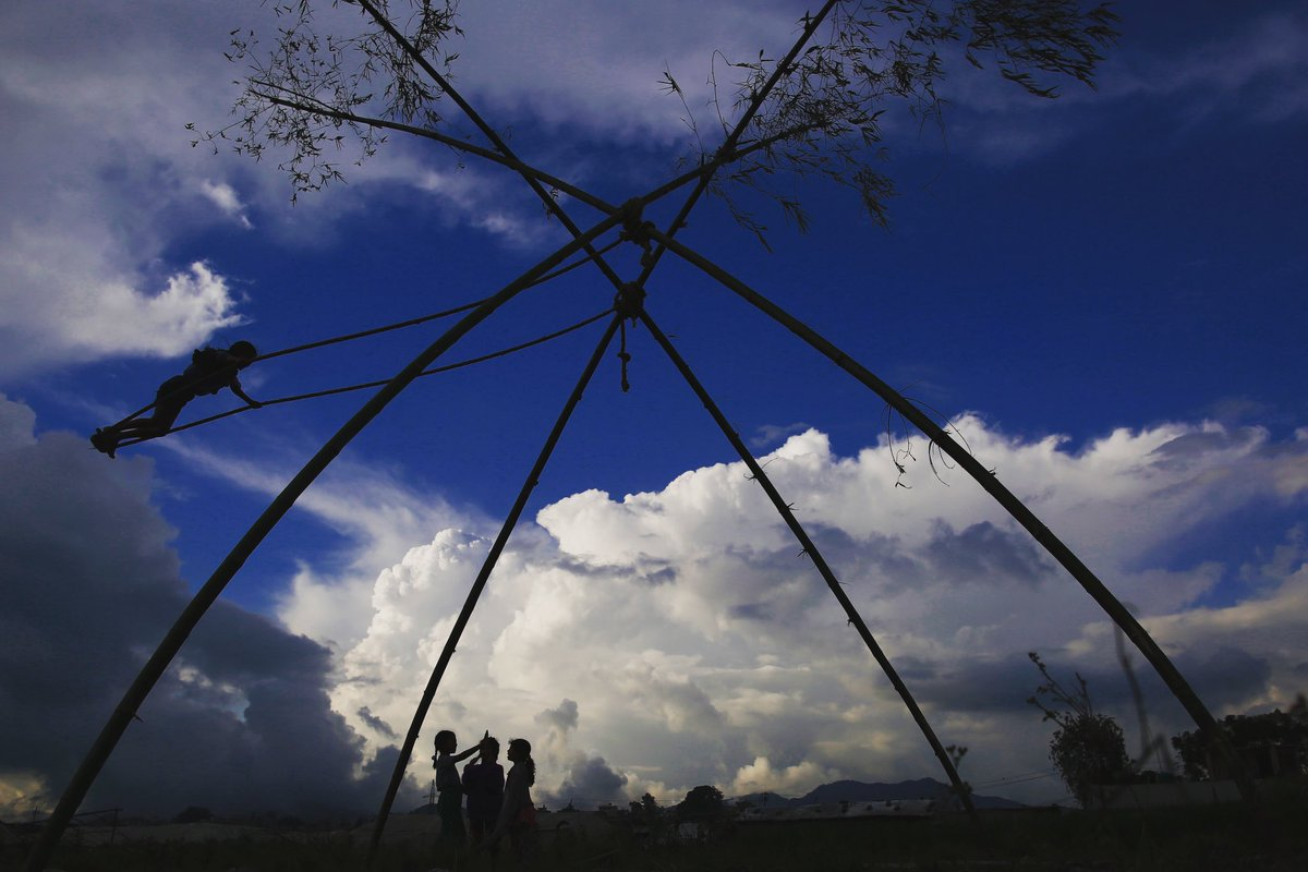 A girl silhouetted plays on a traditional bamboo swing during Dashain festival on the outskirts of Kathmandu, Nepal on Thursday, October 03, 2019.