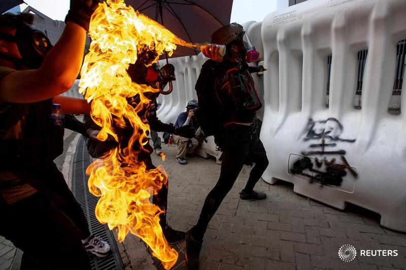 An anti-government protester throws a petrol bomb during a demonstration near the Legislative Council building in Hong Kong. More from the protests: https://t.co/el36hqJT3V 📷@Athit_P https://t.co/akIs8SMjrW