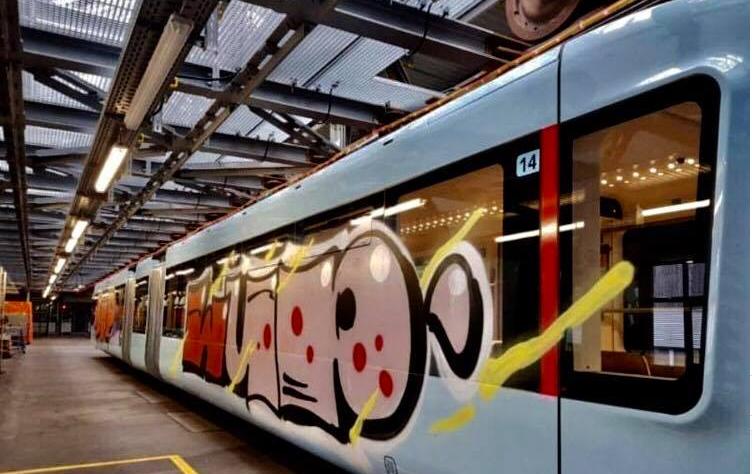 Ein Zug der Schwebebahn in derWerkstatt, auf der Seite ist ein Grafiti Schriftzig zu sehen.