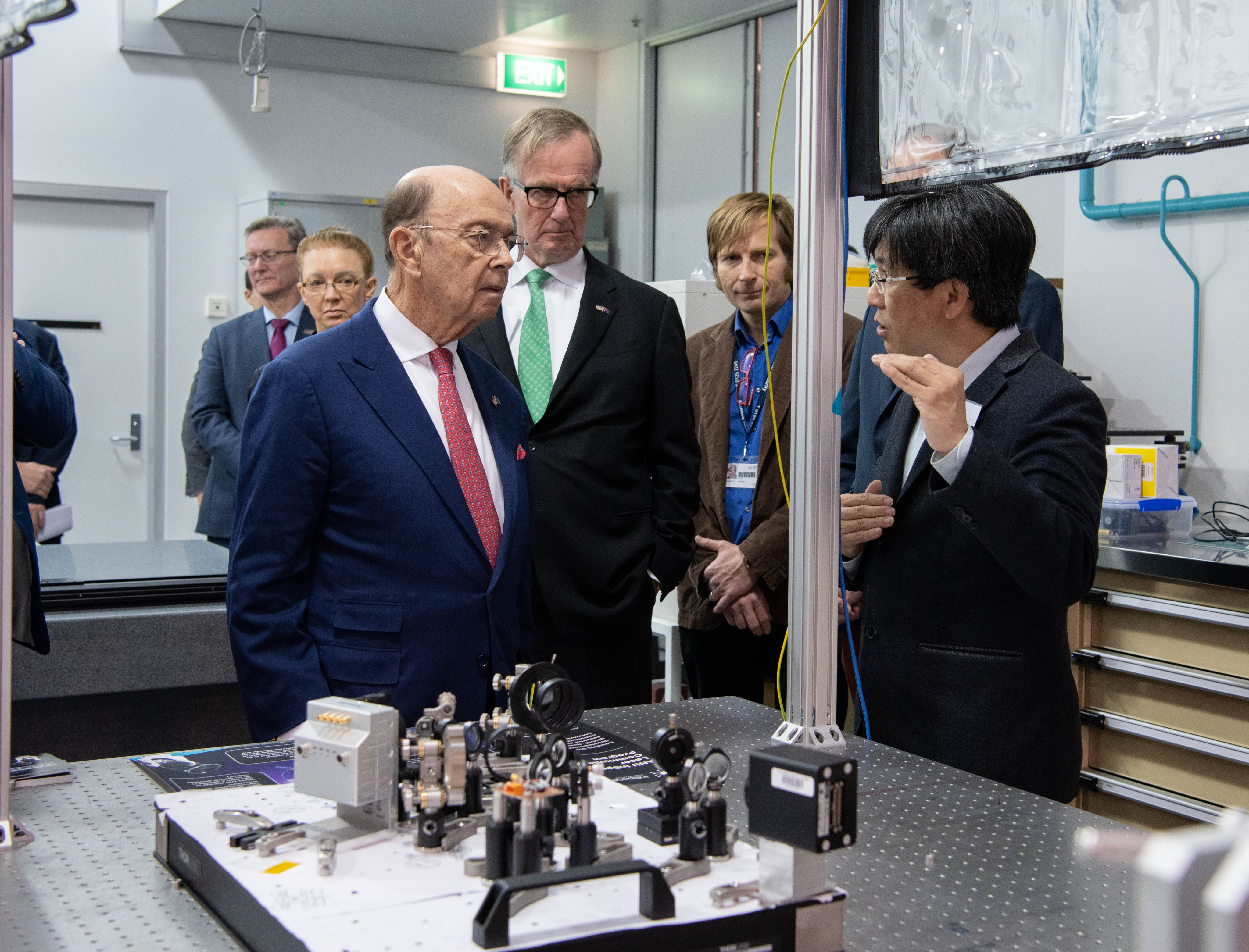 Secretary Ross listening to a person gesturing with equipment in an engineering lab