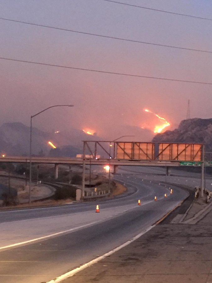 Fire in the hills near a closed freeway interchange where there are no cars and some traffic cones in lanes