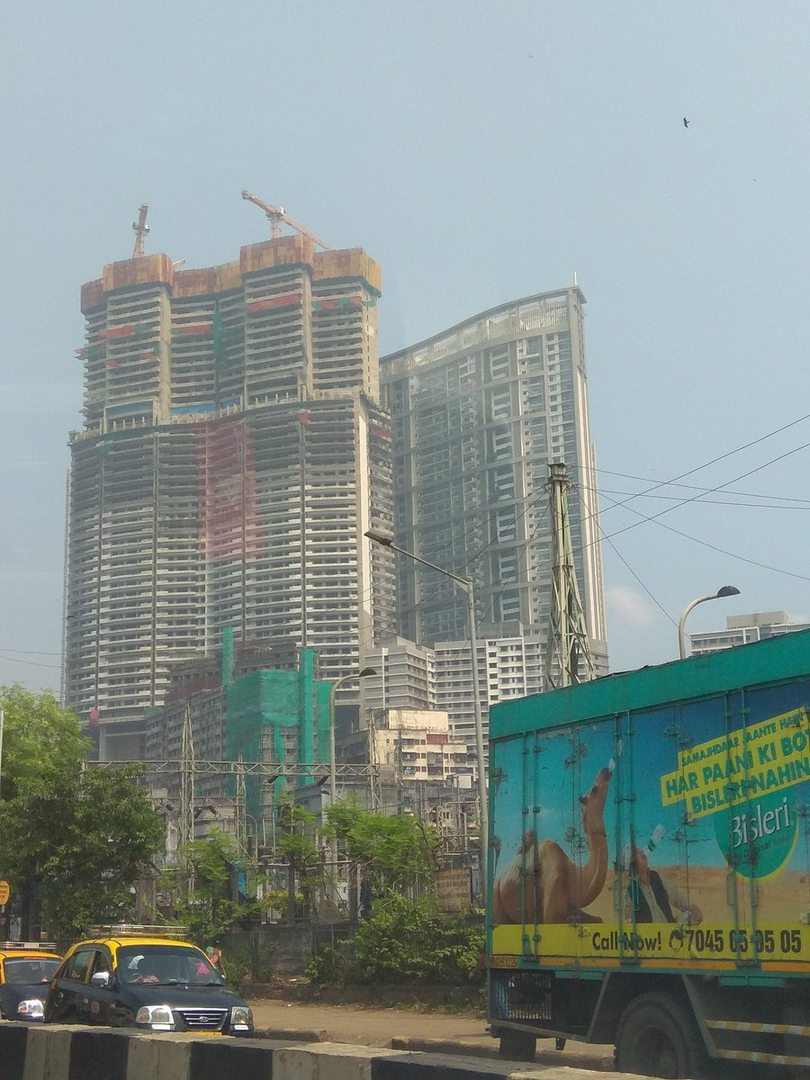 Karma strikes: The Lodha Bellissimo Building (behind) sold to buyers citing racecourse view only to notice within a few months that a Lokhandwala construction was coming in front of it. Today one has filed for bankruptcy and another almost there.