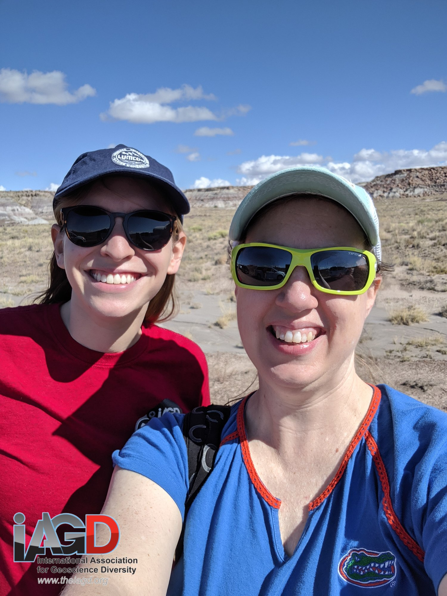 two women wearing sunglasses and hats are smiling. they're outside in the desert.