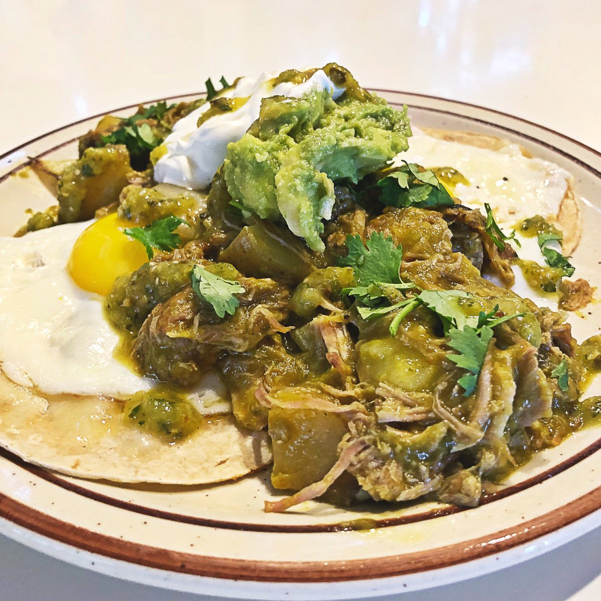 Huevos Verdes: two corn tortillas with melted cheese, two eggs any style, chile verde stew, guacamole and sour cream.