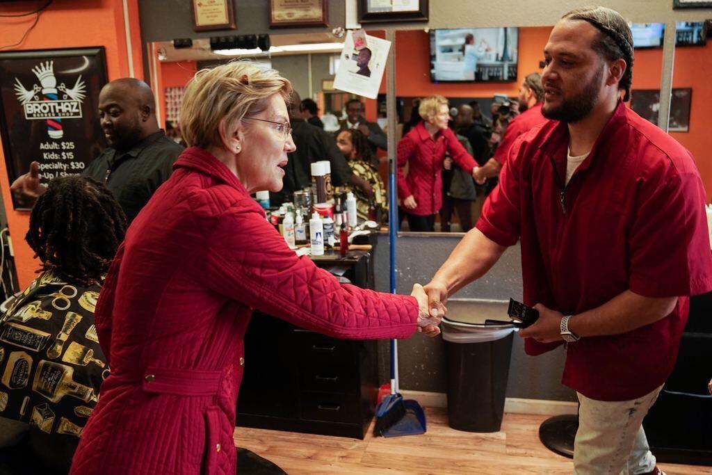 Elizabeth Warren shakes hands with an employee of Brothaz Barber Shop in Waterloo, Iowa.