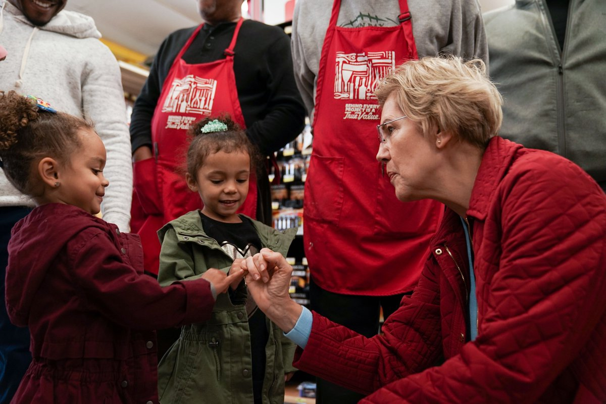 Elizabeth Warren makes a pinky promise with a little girl.