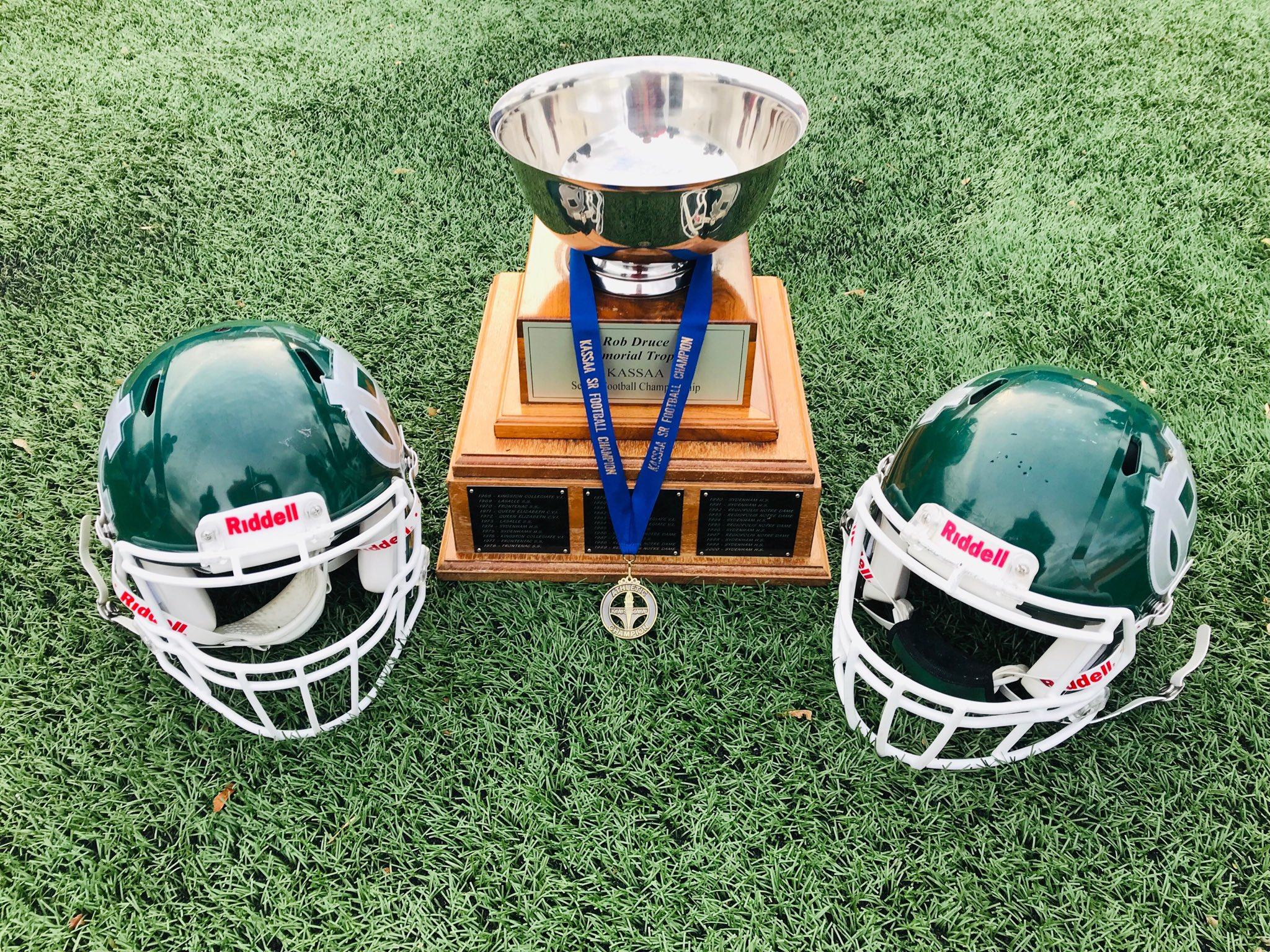 Two Football helmets and a trophy with medal attached.