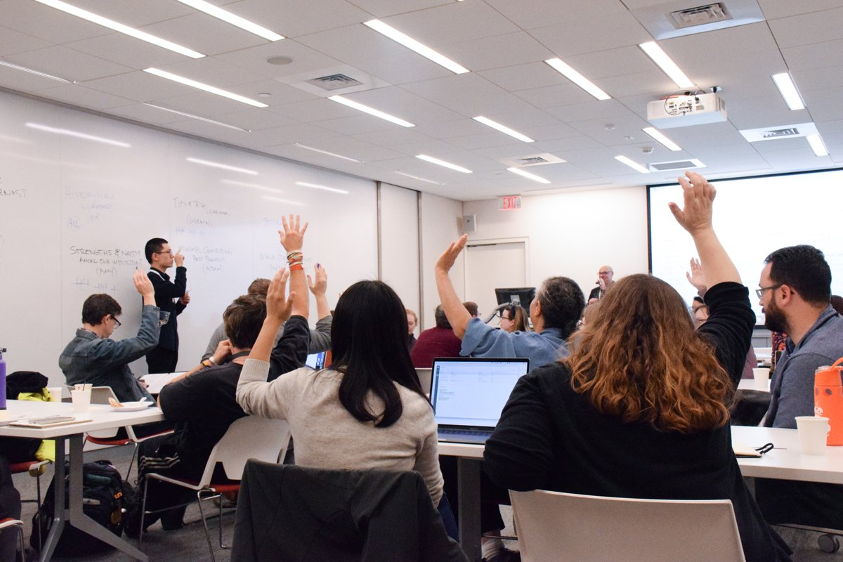 Group of THATCamp participants raising hands while a student moderator standing in front of large white board takes count