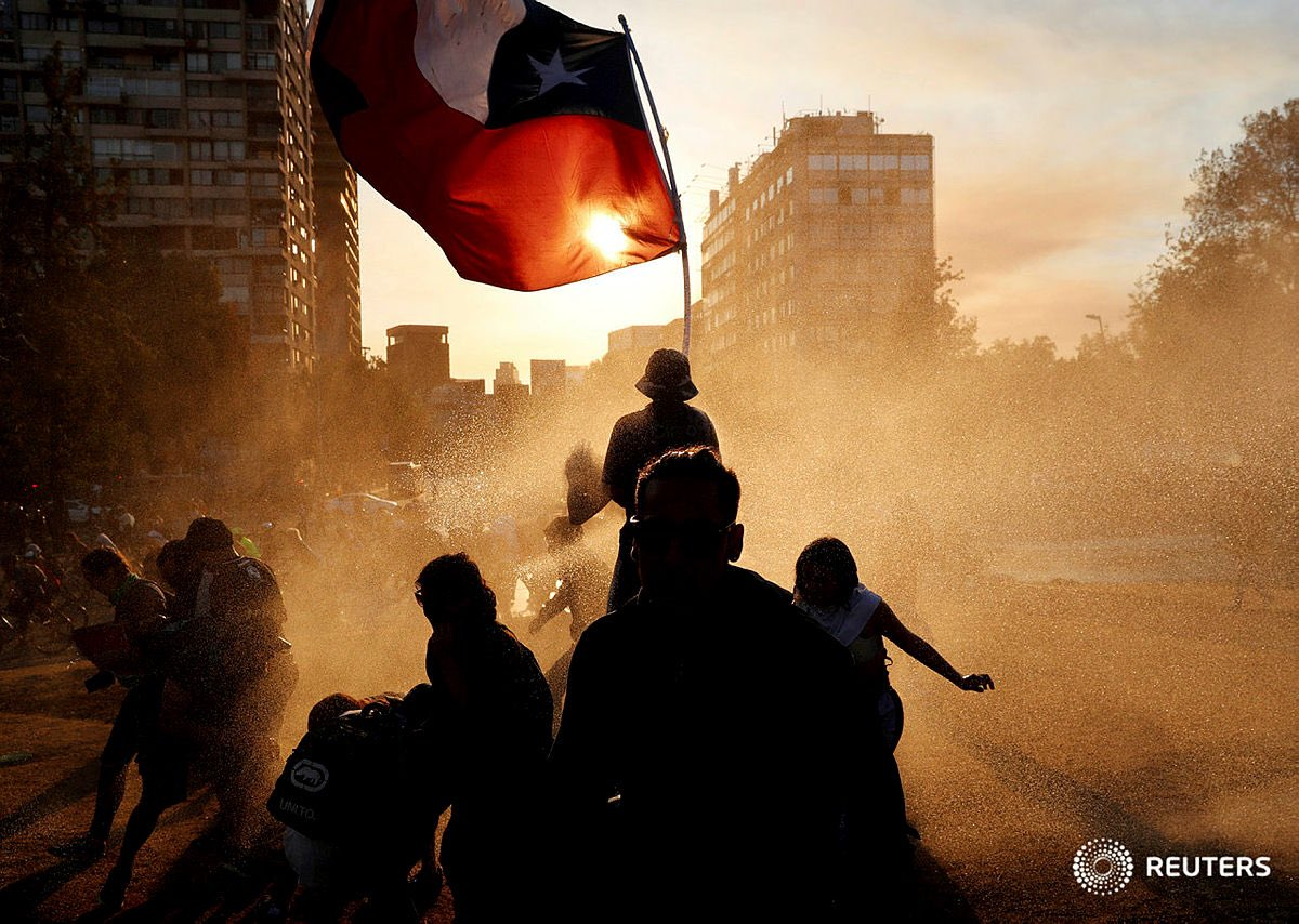 A demonstrator waves a Chilean national flag as others run from tear gas and water cannon at Plaza Italia during a protest against Chile's government in #Santiago , #Chile November 3, 2019. REUTERS/Jorge Silva