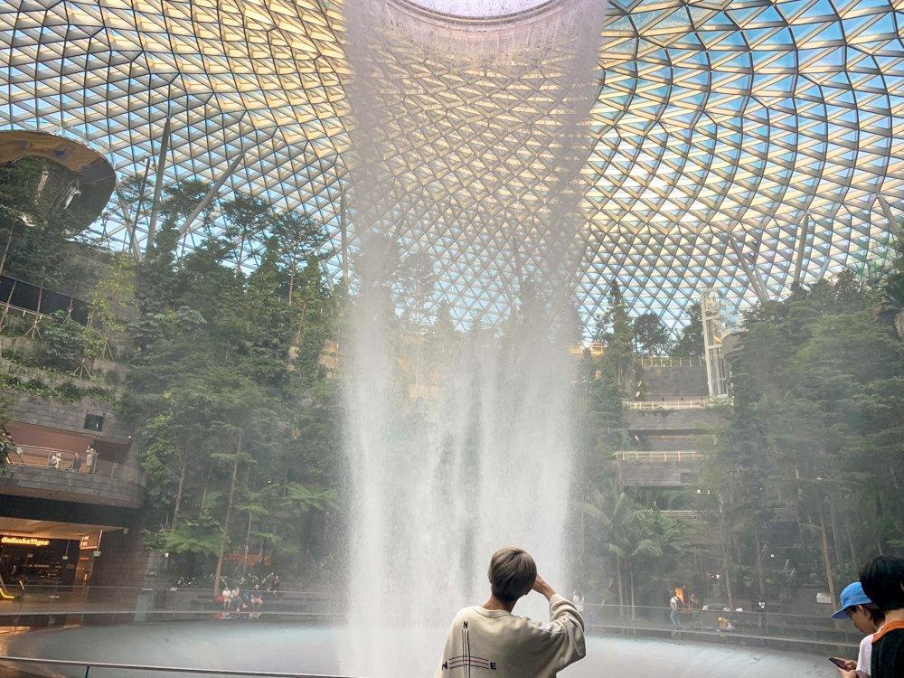 【旅日記_シンガポール編】休憩のあとは、チャンギ空港JEWELをちょっぴり観光。みんなでシンガポールの新観光名所というRain Vortexへ🌿空港の中とは思えない巨大な滝(?)と美しい自然がいっぱいで迫力満点でした!(壮吾くんは電車を見つけてテンションアップ🚃・編集部)