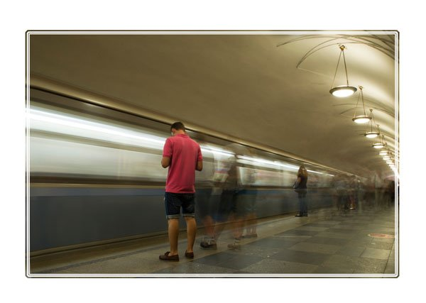 A man on his #phone perfectly still as the #world passes him by on the #Moscow Metro #publictransport #moscowmetro #moscowmetrostation #moscowmetropolitan #Russia #PictureOfTheDay for more see https://www.darrensmith.org.uk/Portfolio