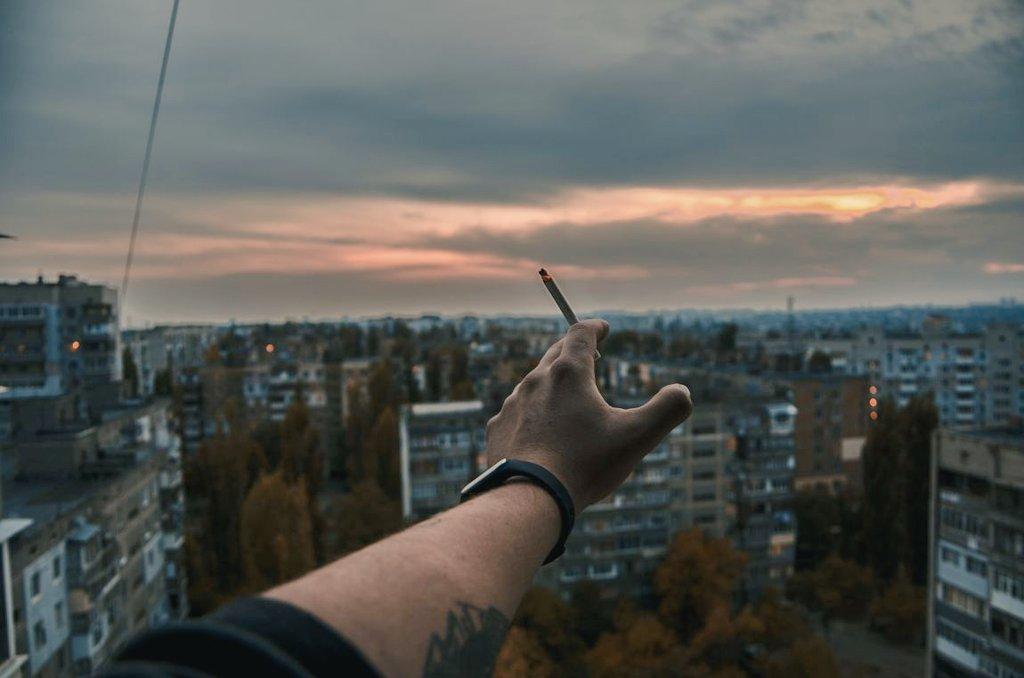 Фото с сигаретой в руках на балконе