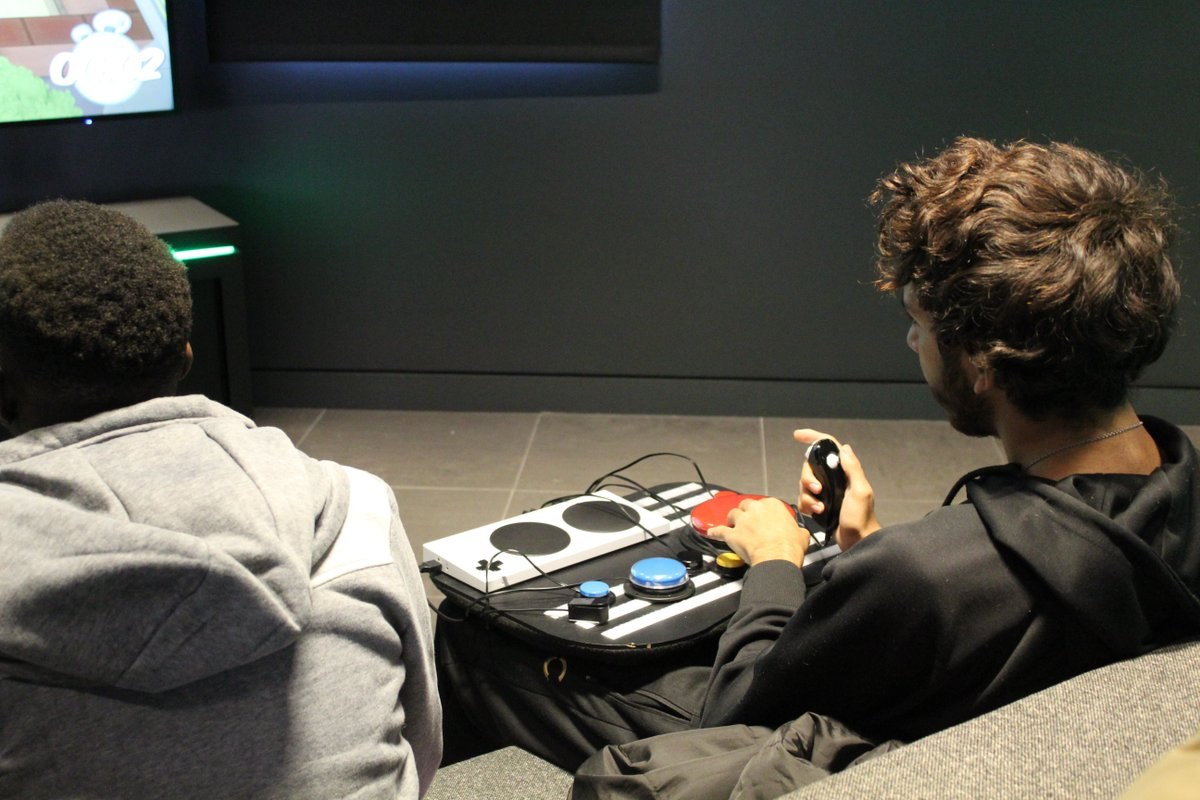 An over the shoulder shot of a man trying out the Xbox adaptive controller setup at the Microsoft store Oxford Circus.