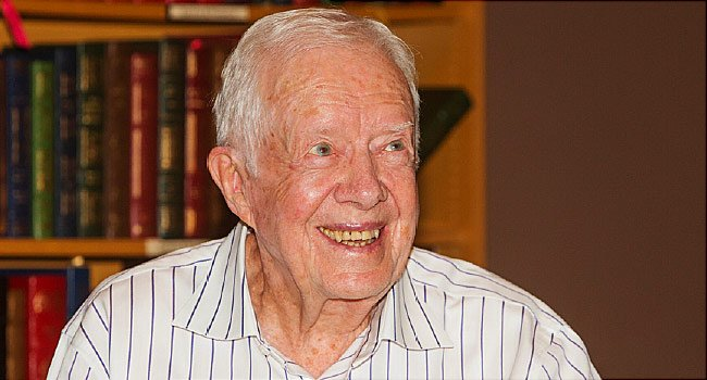 "Former President Jimmy Carter's ""spirits are good and he is up and walking,"" Rev. Tony Lowden told the Atlanta Journal-Constitution. The pastor visited Carter in the hospital Wednesday, according to the paper."