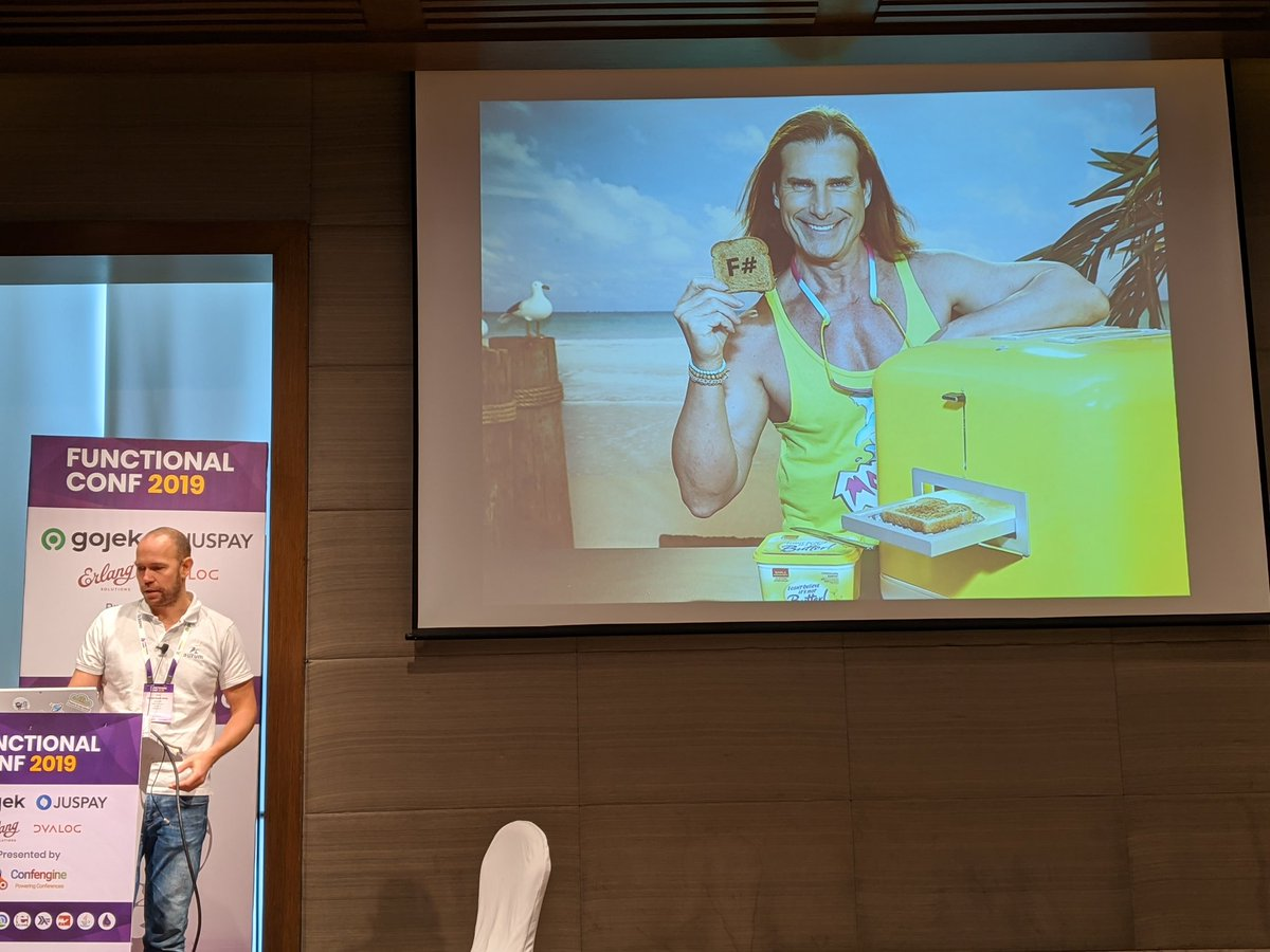 """Attending the Bangalore Functional Conf 2019: """"From a C# monolith to F# actors with Orleans"""". Funny image about sneaking in fsharp into your csharp company. #fsharp #FnConf19<br>http://pic.twitter.com/Y9IViUJw00 – à Welcom Hotel - ITC Hotel"""