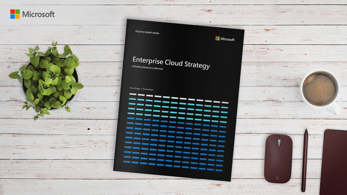 The Enterprise Cloud Strategy book laying on a table besides a potted a plant and a cup of coffee.