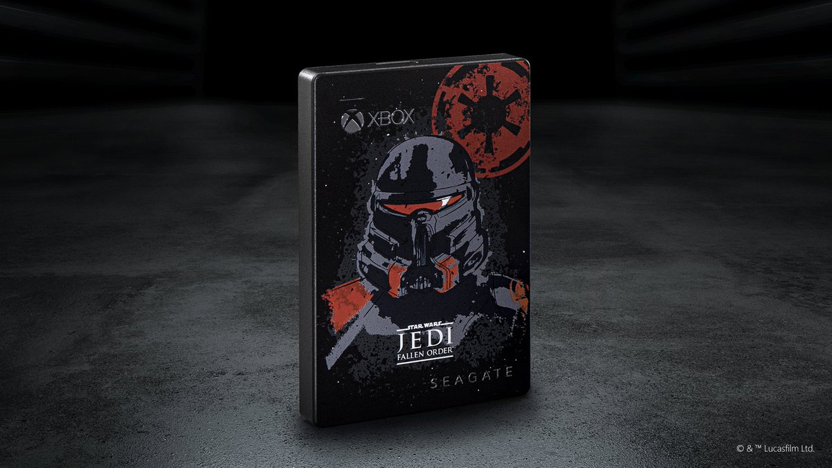 A Star Wars, Empire themed Seagate external hard drive is placed in a dark, dimly lit room. Text on product reads: Xbox. Star Wars Jedi: Fallen Order. Seagate.