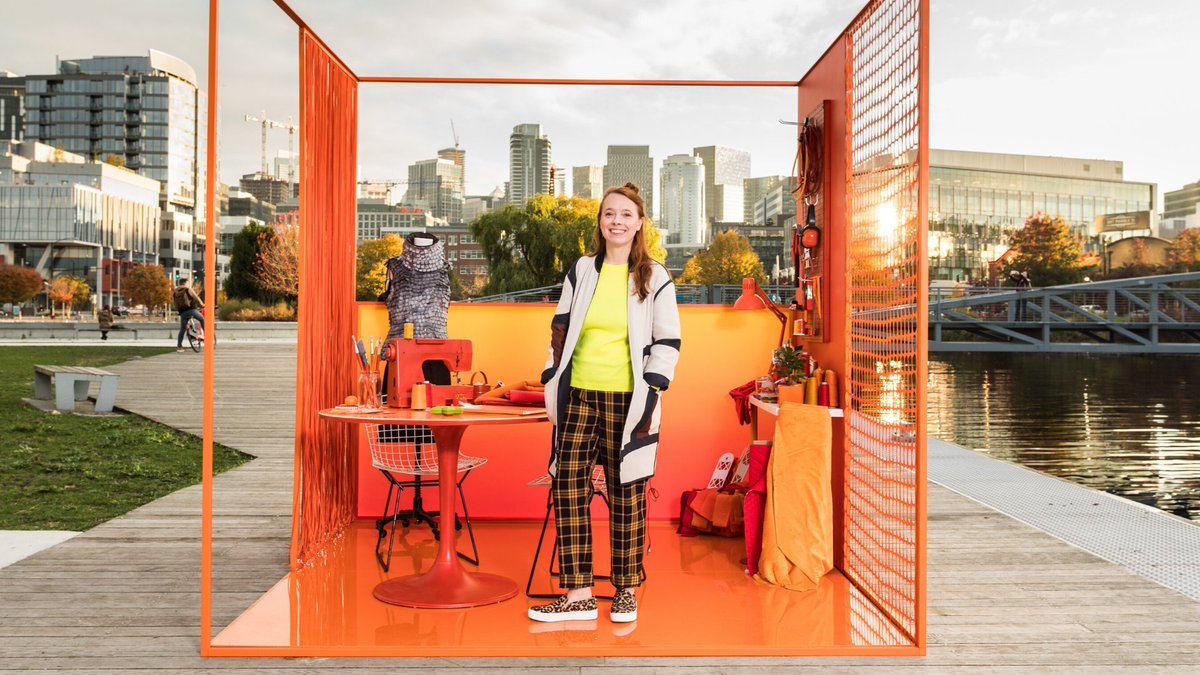 An outdoor photo of South Lake Union in Seattle. In the middle of the walkway is an orange office cube with a young woman standing inside of it.