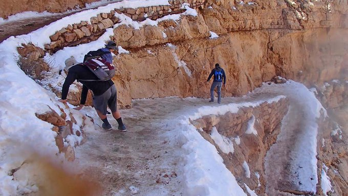 description: several people attempting to descend an icy-covered trail switchback. One person is holding onto the side of the trail to prevent falling.