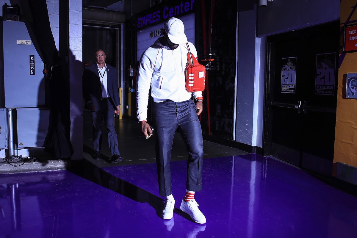 ... courtside ... lebron james wears unknwn x thom browne sweatshirt with red 4-bar stripes, socks, bag, cap and thom browne charcoal grey trousers to the lakers vs. wizards game  @KingJames  @UNKNWN   #thombrowne  #lebronjames