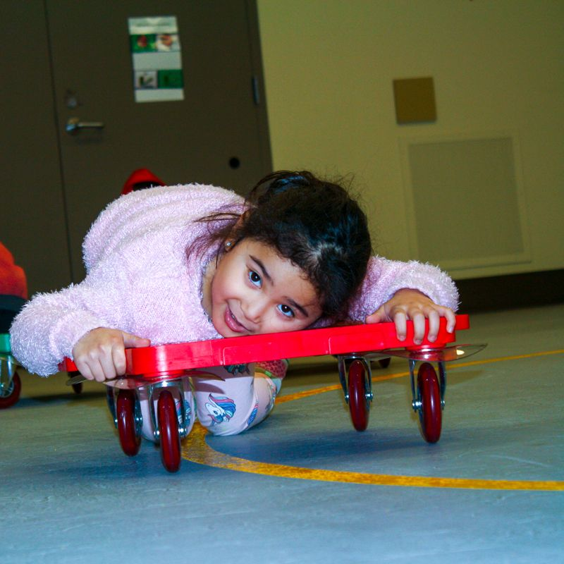 """We love scooter boards! You can sit on them lie on them, move them with your hands or your feet. Children work on coordination and strength and learn concepts like """"stop and go"""" and """"fast and slow"""" - but best of all they are fun! #fun #HelpingKidsSoar #RenfrewES"""