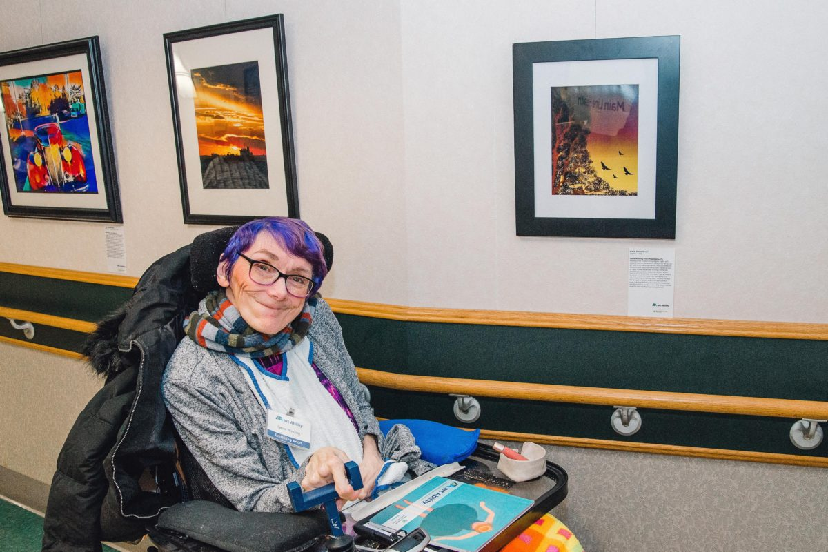 Artist Lynne Walding sits in a wheelchair against a wall with three works of art displayed. She has short purple and blue hair, is wearing black glasses, and is smiling. A black winter jacket hangs on the back of her wheelchair.