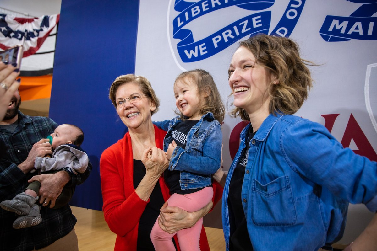 A young girl makes a pinkie promise with Elizabeth Warren.