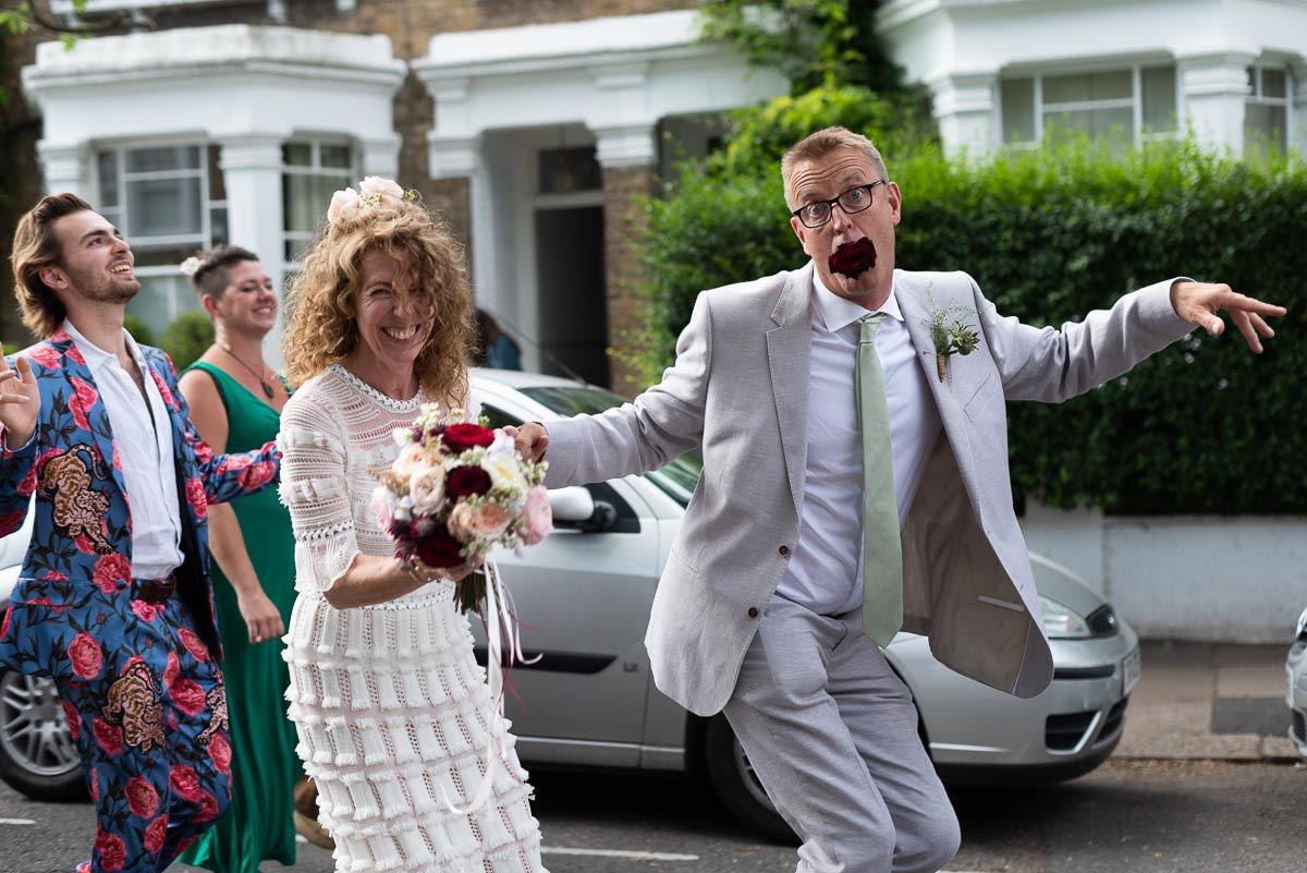 Will and Kitty enjoying their Wedding Procession from @CoLQueensPark #QueensParkLondon to @HugosQP. Will, ever the improviser, repurposed his detached Rose Pinhole as a comical mouth prop. #weddingphotographer #weddingphotographers #weddingphotographeruk #lewesweddingphotographer
