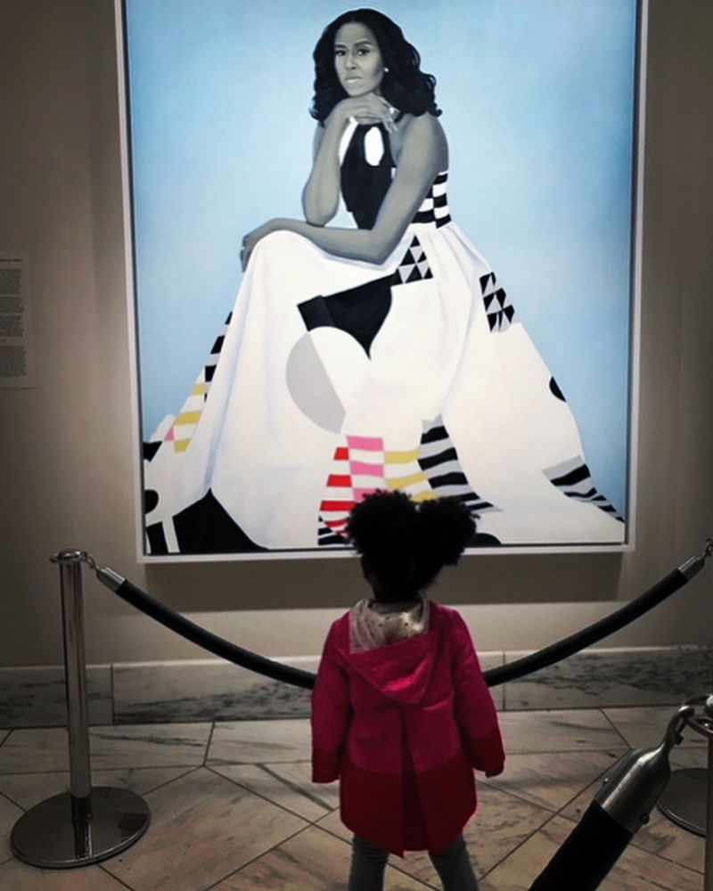 "Three-year-old Parker Curry, awestruck by Amy Sheralds portrait of Michelle Obama, in an image that went viral. Now the subject of ""Parker Looks Up: An Extraordinary Moment,"" a children's book Parker co-authored with her mother #womensart"