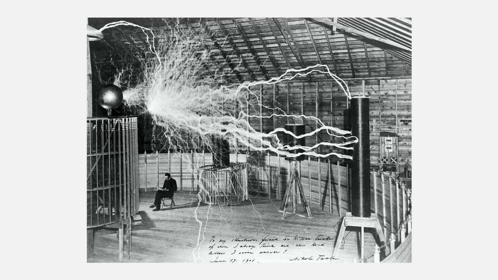Nikola Tesla calmly reading while his magnifying transmitter let loose a torrent of streamers. This photograph was created by Dickenson Alley. It is a double exposure on a single glass plate: Tesla was first photographed and then the magnifying transmitter was turned on. ⚡️