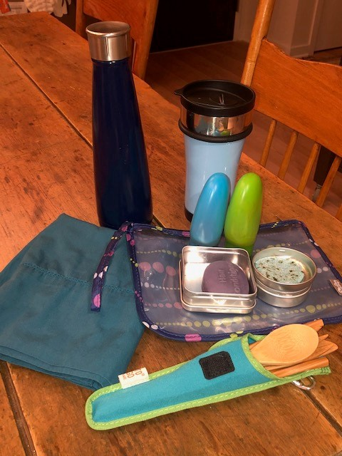 A travel kit containing reusable bags, shampoo and conditioner containers, water and coffee containers, tins for soap and solid shampoo, and a set of bamboo utensils.