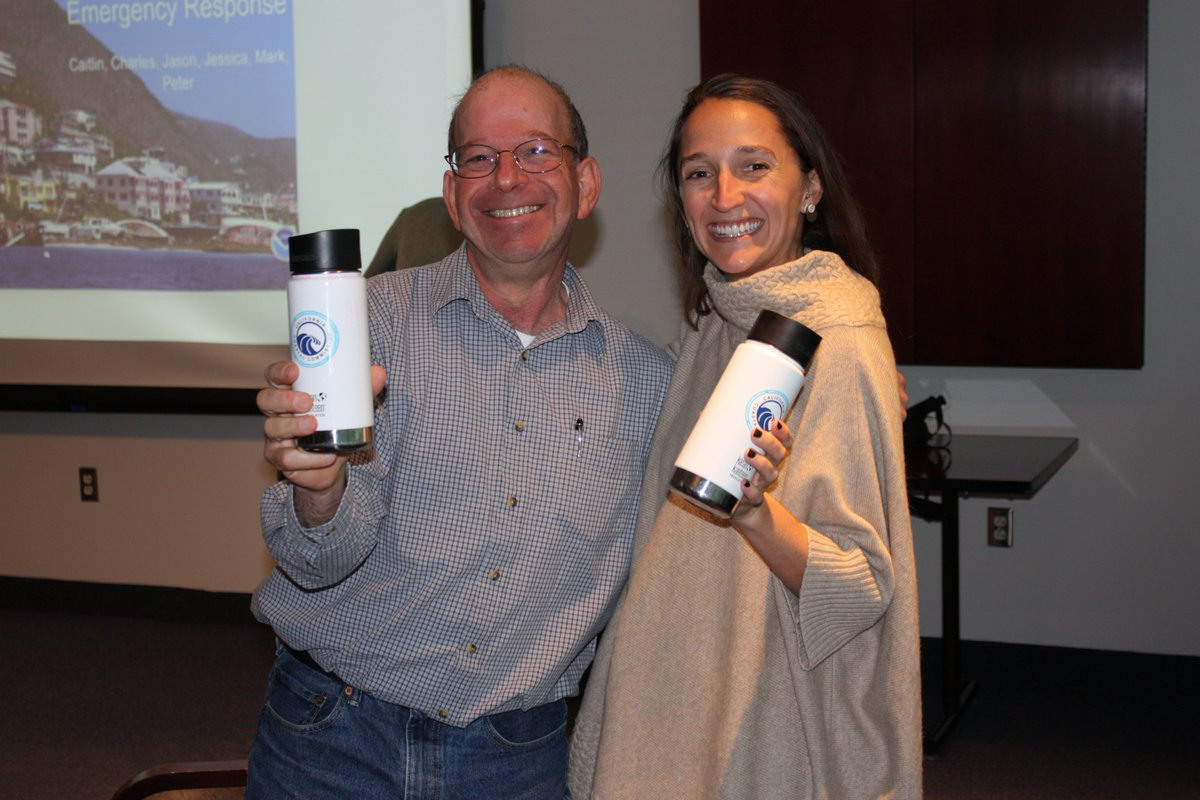 Two people smile while they hold up their reusable travel mugs.