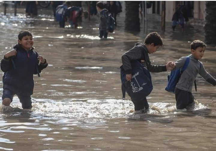 Palestinian students walk in a street flooded by rain water, in Jabalia, northern of #Gaza Strip. ✌️