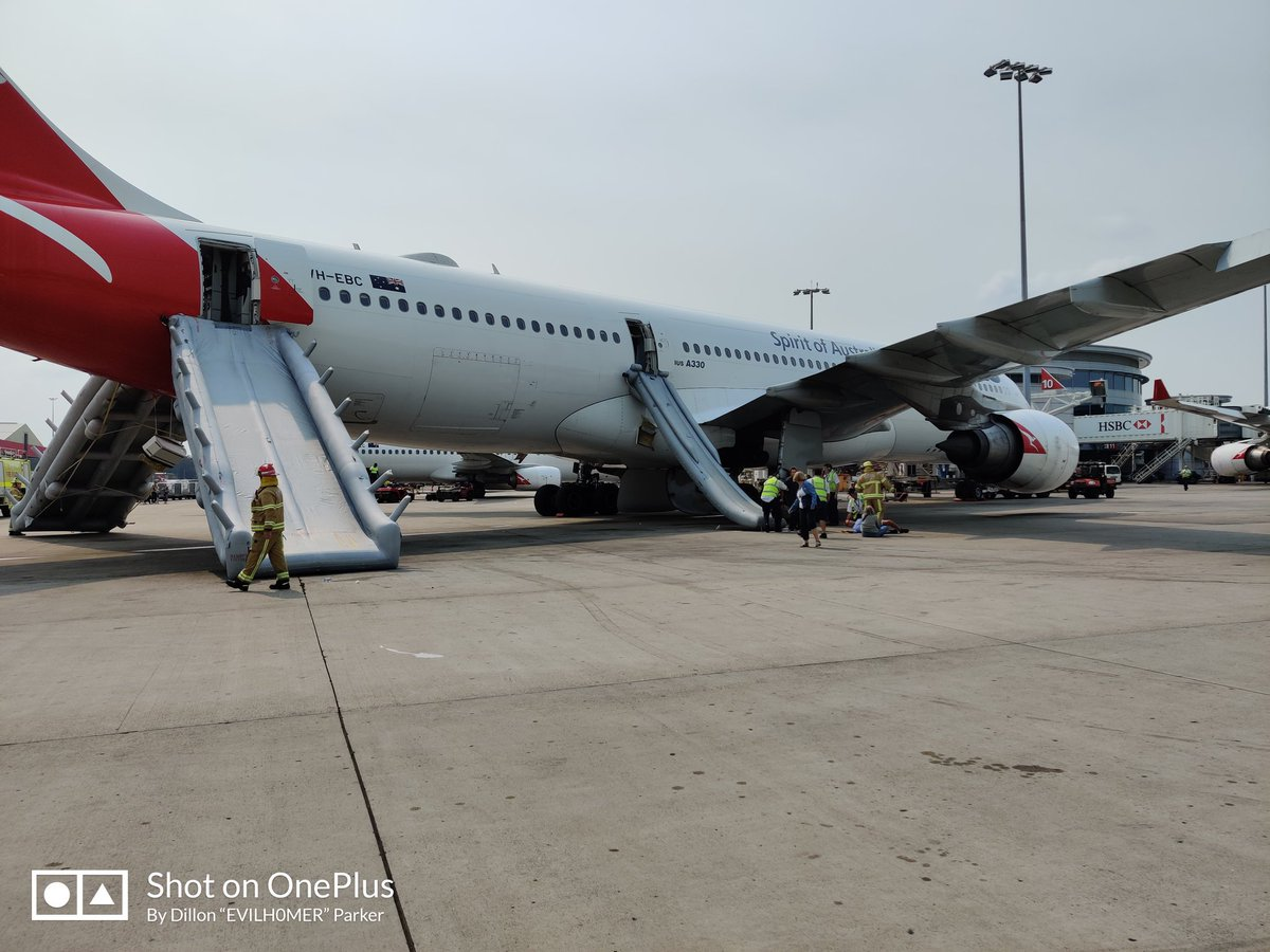 Passengers evacuate Qantas plane using emergency slides at Sydney airport